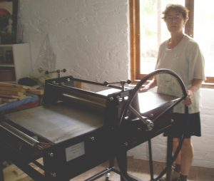 Jacky Lowry, artist and printmaker, with Grace, the printing press newly installed.