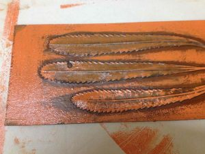 Collagraph printing plate with a surface roll of relief ink.