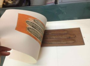 The Reveal - Paper being removed from a freshly-printed collagraph plate - The Reveal